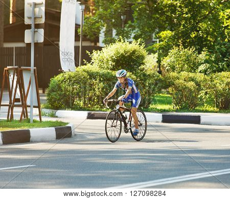 Female sportsman cyclist riding racing bicycle. Woman cycling on countryside summer sunny road or highway. Training for triathlon or cycling competition.