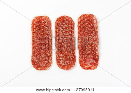 thin slices of salami arranged on white background