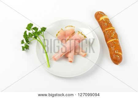 rolled slices of asparagus coated ham with parsley and bread roll on white plate
