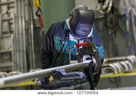 Industrial operator setting  computer controlled process of orbital welding machine in inox pipes manufacturing workshop.
