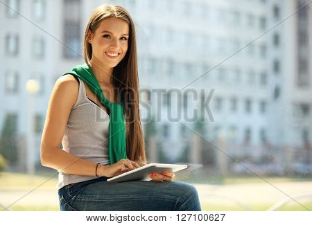 Smiling young women using digital tablet in the office