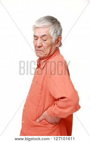 portrait of senior Japanese man suffers from lumbago on white background