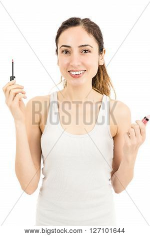Smiling friendly caucasian woman showing lipstick bottle in her heands. Isolated on white background.