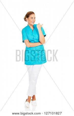 Young female doctor showing something by thumb