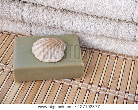 Natural olive soap bar scallop shell and terry towel on the bamboo mat