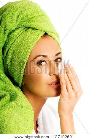 Woman in bathrobe removing makeup