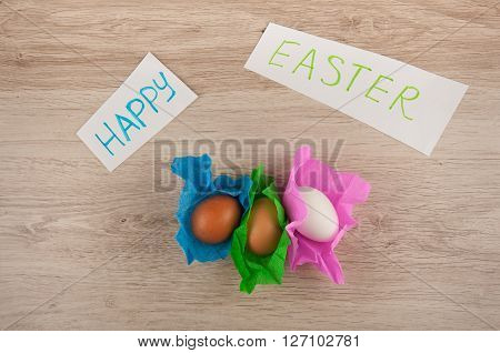 words easter on paper titles and three chicken eggs in colored paper wrapper laying on wooden table