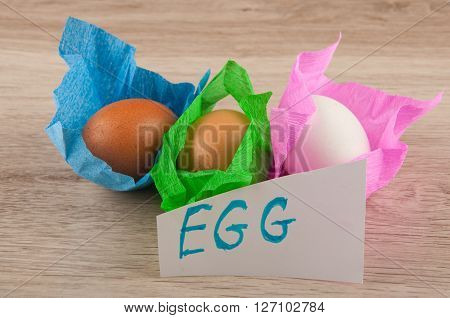 title and three chicken eggs in colored paper wrapper laying on wooden table