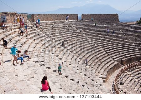 PAMUKKALE, TURKEY - September 13, 2015: Tourists regard antique amphitheater in the ancient city of Hierapolis. Pamukkale, Turkey.  Pamukkale is included in the UNESCO World Heritage List.