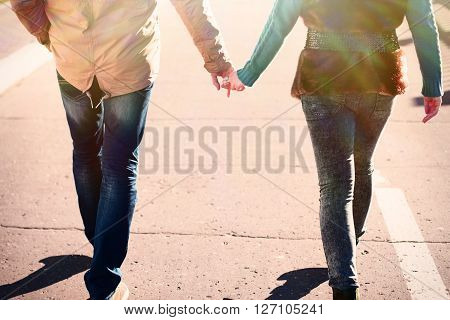 Young couple in the spring in the city, relax, love each other, happy family, the idea of the style of the concept of love relationship in fall clothes holding each other's hands walking down the street