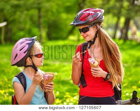 Bikes cycling girls with rucksack cycling eating ice cream cone in summer park.
