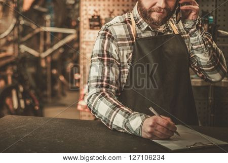 Stylish bicycle mechanic takes order by phone in his workshop.