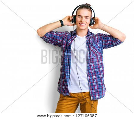 Young man enjoying music on his headphotes, listening to music. Handsome young stylish man in headphones standing against white background and smiling