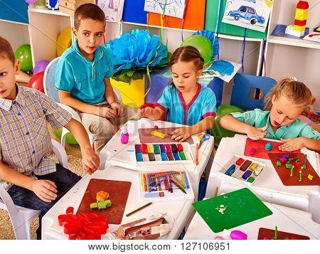 Group kids mold from plasticine  in kindergarten .