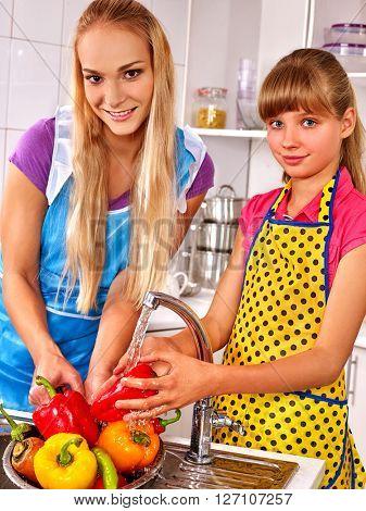 Children washing fruit at kitchen.