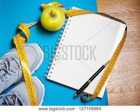 Sneakers centimeter green apple notebook. Weight loss healthy lifestyle concept