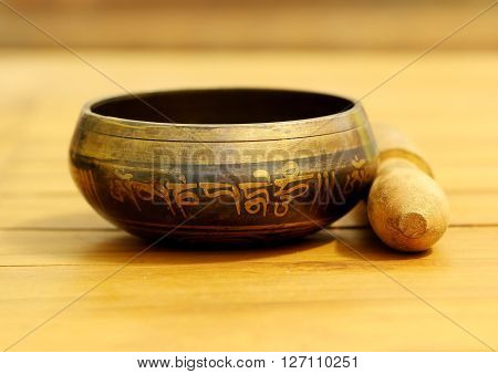 Tibetan singing bowl made of brass on teak wood table.