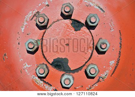 Closeup of eight tighten screws symmetrically arranged in a circle