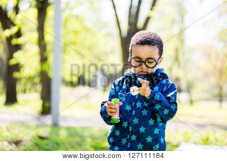 Boy blowing bubbles at the park. black boy
