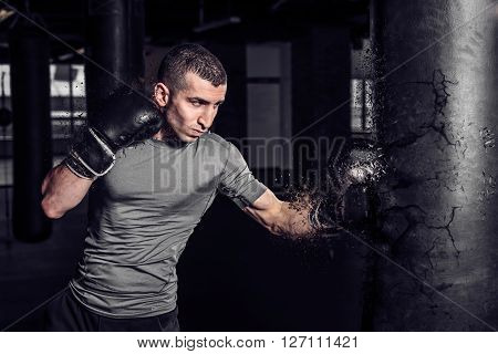 Boxer punch punching bag exploding in gym. Young strong man stabs and trains in the gym.
