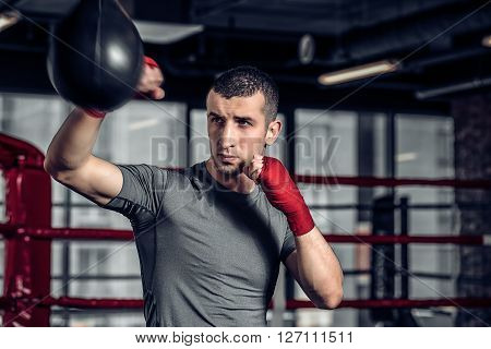 Young Male boxer using a punching bag in gym. Boxer hitting punching speed bag in gym, head and shoulders. Athlete with red boxing bandages.