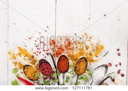 Various colorful spices on wooden table, top view.