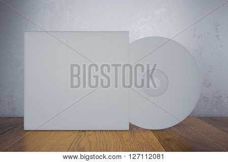 Light gray black compact disk with cover on wooden table and concrete wall background. Mock up 3D Rendering