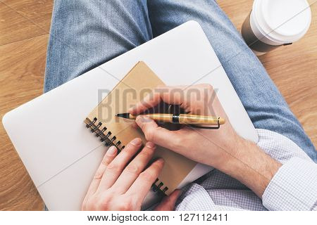 Top view of man writing in aged notepad placed on closed laptop and coffee. Wooden background.