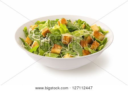 classic Caesar salad in a deep white plate isolated