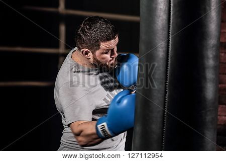 Portrait of Boxer boxing with punching bag. The athlete trains and prepares for boxing.