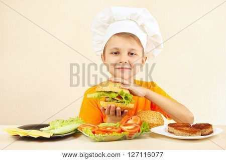 Young smiling chef in chefs hat enjoys a cooking tasty hamburger