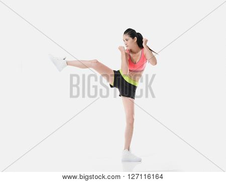Confident young woman doing boxing moves on white background