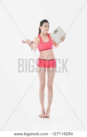 asian woman holding scales with a tape measure on a white background