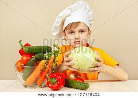 Little boy chooses vegetables for salad at the table
