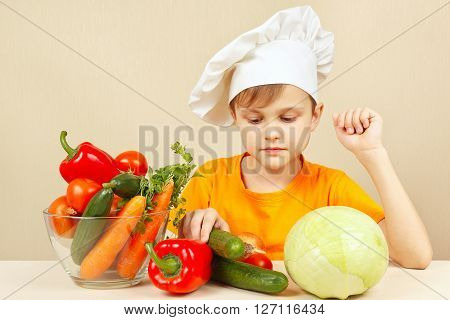 Little chef chooses vegetables for salad at the table