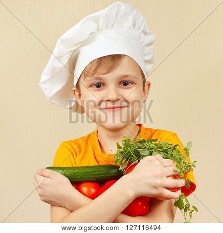 Young funny chef with the fresh vegetables