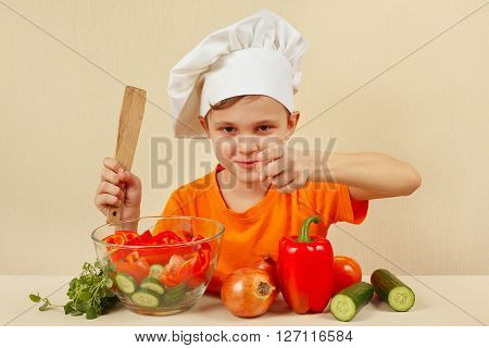 Young smiling chef shows how to cook a vegetable salad
