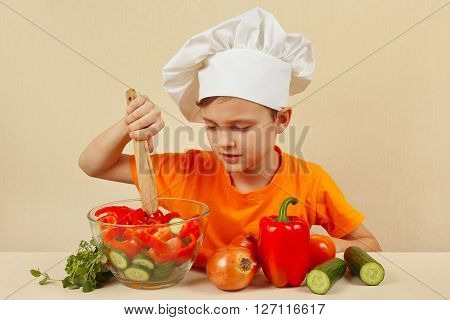 Little boy in chefs hat mixing the vegetables in a bowl with salad