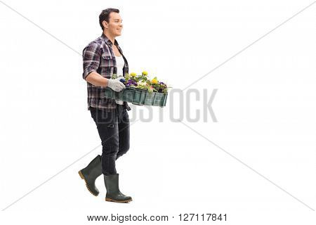 Profile shot of a young man carrying a rack of flowers isolated on white background