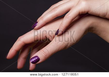 Close up of crossed over female hands decorated with purple fingernail paint over black