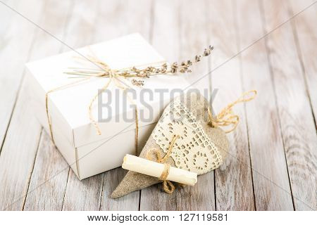 White gift box with rustic twine and a sprig of a lavender with hand