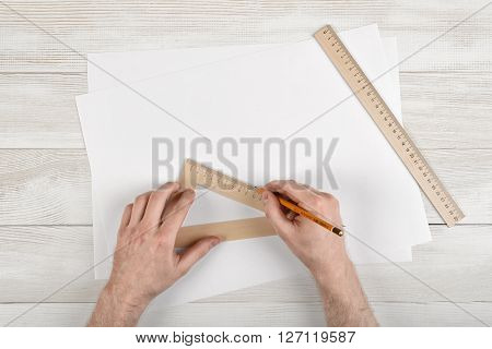 Close-up man hands  during measuring process by triangle centimeter ruler. Work place of constructor with simple centimeter ruler and white paper.