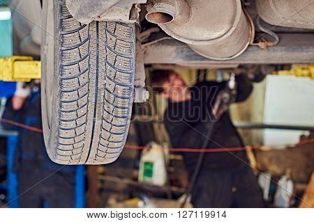 Car repairing in workshop. Mechanics are repairing a front car suspension
