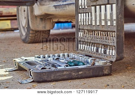 Open toolkit for car repair. Mechanic is going to begin repairing the car. He has put his toolbox near a car
