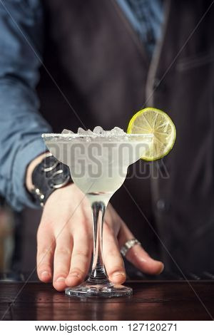 This is closeup of barman serving cocktail margarita.