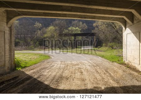 Looking out of a bridge tunnel at a railroad bridge.