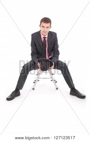 Boy in black suit sits on a chair isolated on white