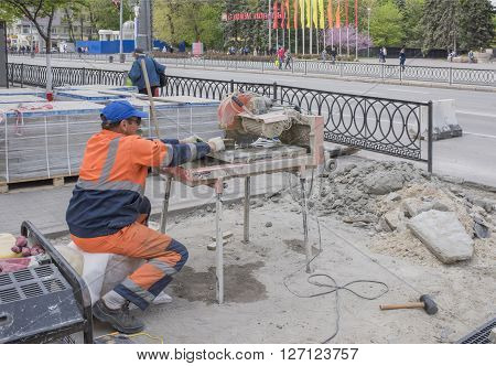 ROSTOV-ON-DON RUSSIA- APRIL 24- Worker cuts paving tiles on the machine tool on April 242016 in Rostov-on-Don