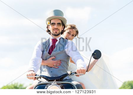 Wedding groom and bride driving motor scooter having fun