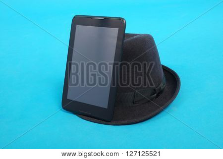 Tablet PC is at the felt hat isolated on blue background